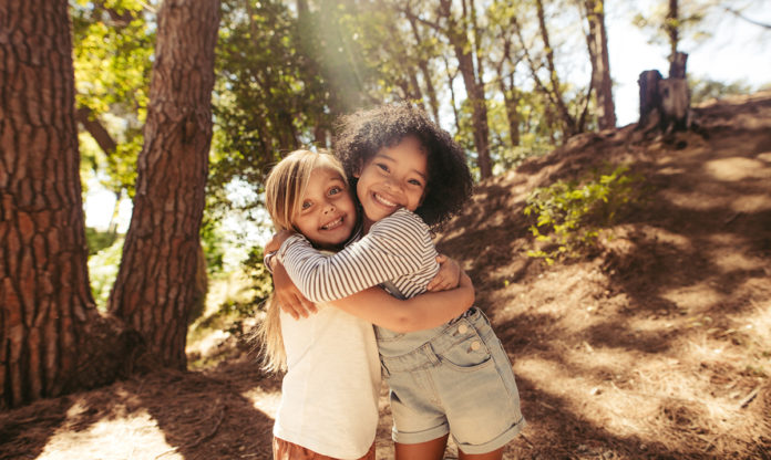 Two little girls hugging and smiling