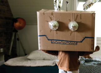Kid with a decorated cardboard box on their head