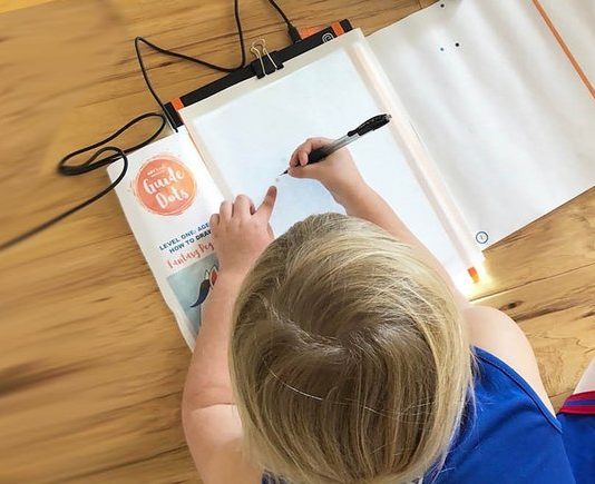A kid drawing with Guide Dots