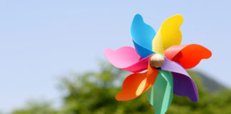 A pinwheel in front of a blue sky and trees