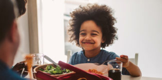 A child smiling while eating