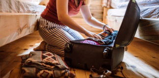 A woman in pajamas packing a suitcase