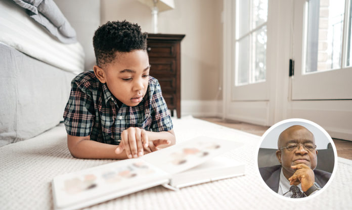Little boy reading on a floor. Image of Dr. Curtis L. Ivery in the corner