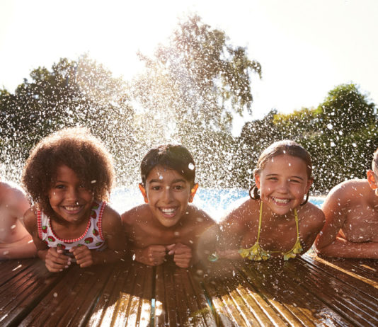 Group of kids of different races playing in a pool together