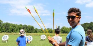 Kid holding arrows at camp