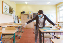 A teacher in a mask measures between desks