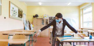 A teacher in a mask measures between desks