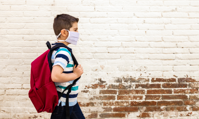 Kid in a mask walking with a backpack