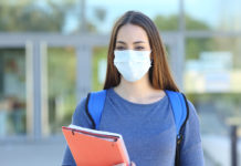 A teenager wearing a mask and holding a notebook