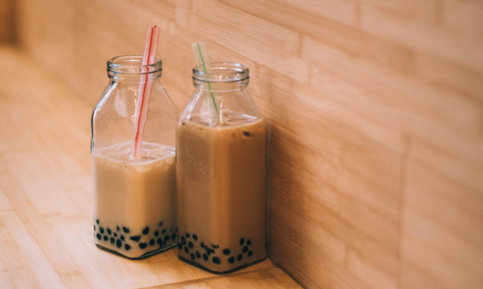 Teo containers of bubble tea next to a wood wall