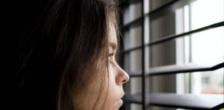 A young girl looking out closed blinds