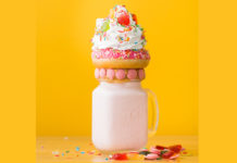 A milkshake topped with a donut, whip cream and candy on a yellow background