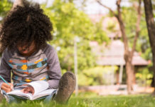 Child outside writing in a book