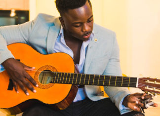 a Black man playing a guitar
