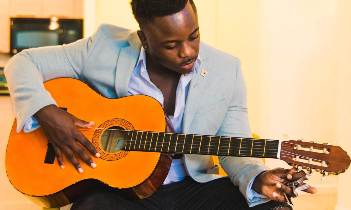 a Black man playing a guitar