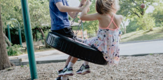 Two kids playing on a tire swing