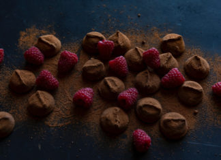 Bonbons covered in chocolate powder and surrounded by raspberries