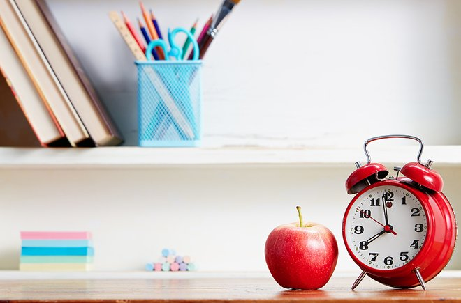An organized space with an apple and a red alarm clock