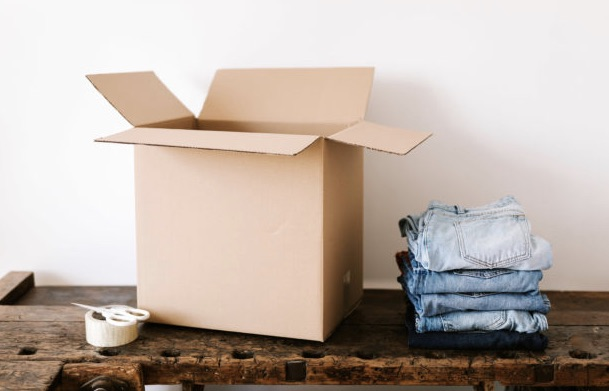 Pants and tape next to a move-in box