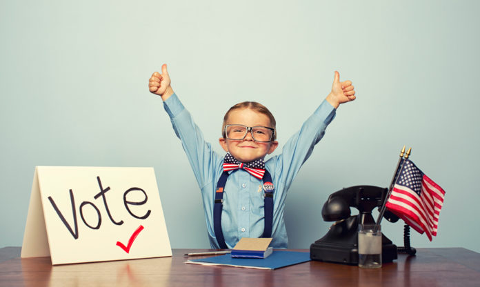 Kid in a bow tie puts thumbs up in the air behind a desk