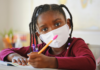 Young girl wearing a mask holding a pencil and looking at the camera