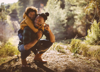A man giving a child a piggy-back ride up a mountain