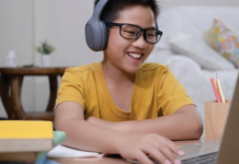 Kid smiling while on a computer