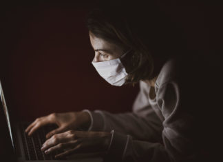 Girl in a mask on her computer