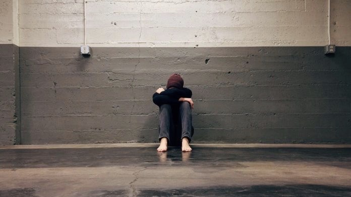 Barefoot teen sitting up against a wall with their head in their arms