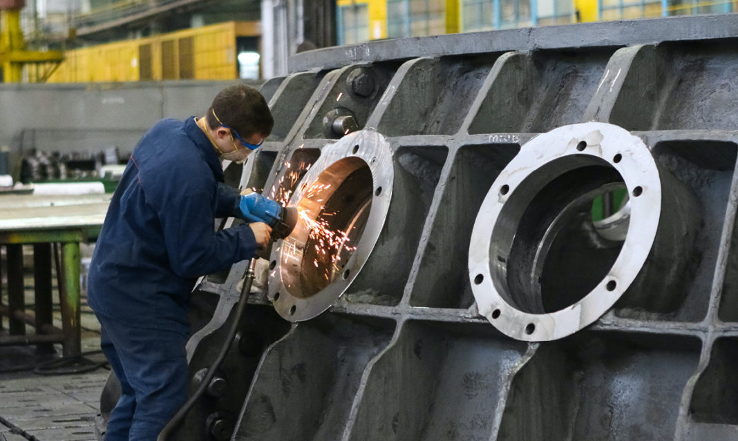 A man welding a large piece of machinery