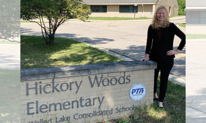 Megan Sidge posing with the sign for Hickory Woods Elementary