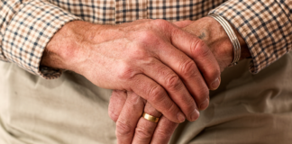 A pair of old hands folded on a cane