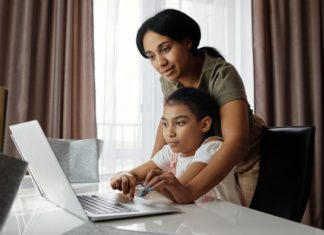 Woman helping a young girl on a laptop