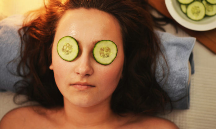 Woman at a spa with cucumbers on her eyes