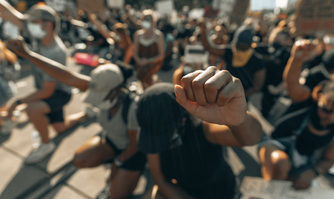 Group of people kneeling with fists in the air at a protest