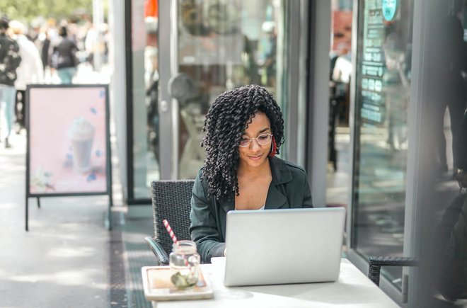 Woman on a laptop in a city