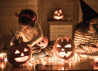 Two girls in costume carving pumpkins