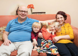 Christine Dubois and family sitting on her couch