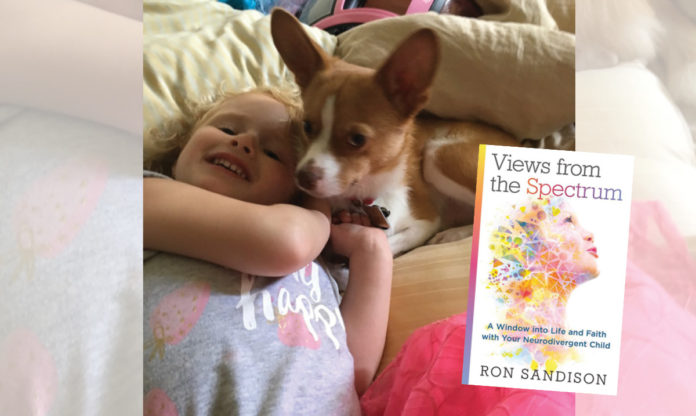 Makayla and her dog playing. Cover of Ron Sandison's latest book in the foreground