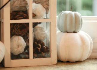 White pumpkins stacked next to a lantern filled with fake pumpkins and pinecones