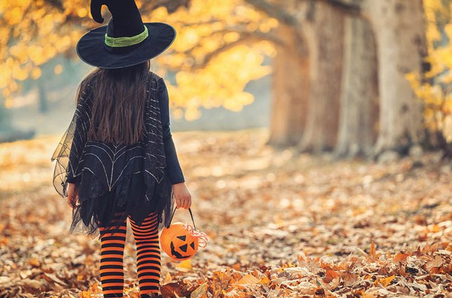 The back of a child, dressed as a witch, walking among yellow and orange trees.