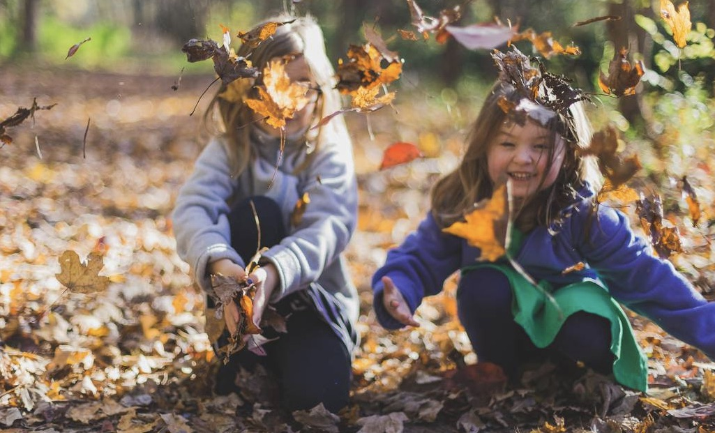 Two little girls laughing while playing in a pile of leaves