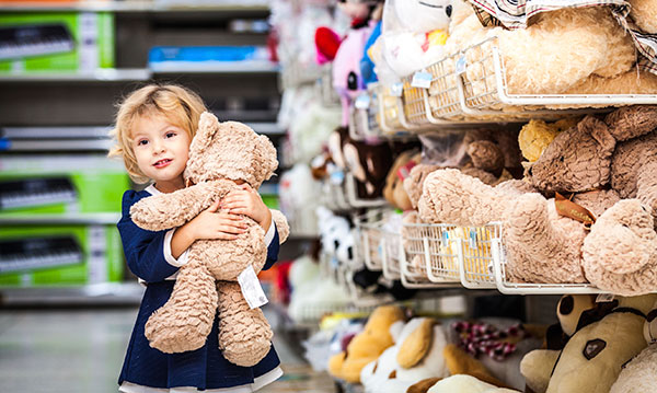 Child hugging a bear in a toy store