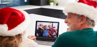 An elderly couple wearing Santa hats Zoom calling a young family of four