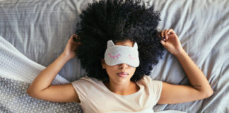 Woman in bed wearing a light-blocking eye mask