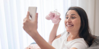 Woman holding up a pair of pink baby booties while on her phone