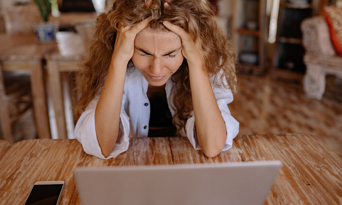 Woman crying with her head in her hands while looking at a laptop