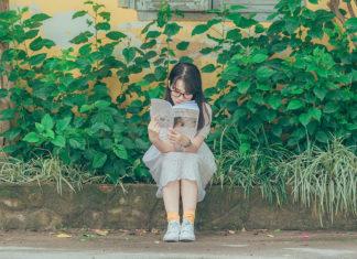 Tween girl reading outside