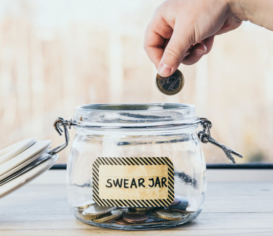 A hand dropping coins into a swear jar
