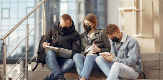 Three college-aged kids sitting on steps while wearing face masks